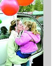 Susan Rizk kisses her daughter after returning home following a nearly two-month stay at Washoe  Medical  Center. Rizk was attacked at her South Lake Tahoe home by a man wielding a sword.  Jim Grant/Appeal News Service