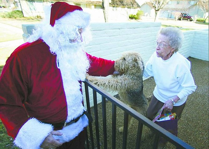 BRAD HORN/Nevada Appeal Santa Claus greets Hilda Christensen and her dog MacDuff at her Carson City home on Friday. Gwen Currie, of Friends to All, and Santa Claus brought gifts to the area's seniors including treats for their animals.