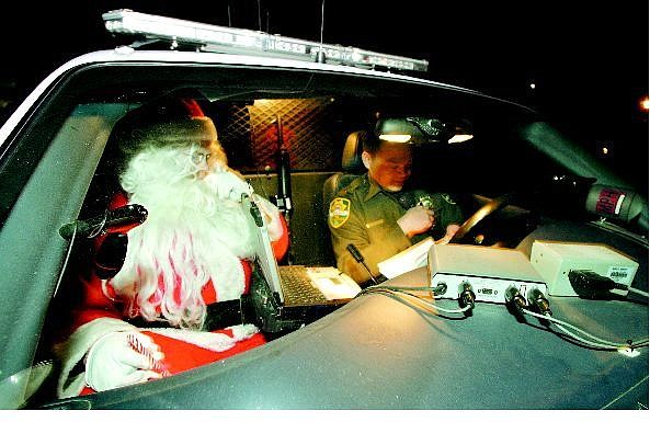 BRAD HORN/Nevada Appeal Carson City Sheriff's reserve deputy Homer Dagdagen and Santa Claus get ready to bring gifts and Christmas cheer to a Carson City family on Christmas Eve.