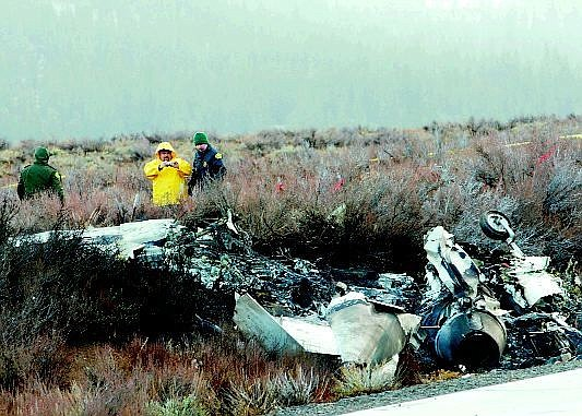 Photo by Ryan Salm/Sierra Sun Investigators examine remnants of the wreckage after a private jet crashed and burst into flames Wednesday. Both occupants were killed when the jet crashed as it tried to land at Truckee Tahoe Airport north of Lake Tahoe.