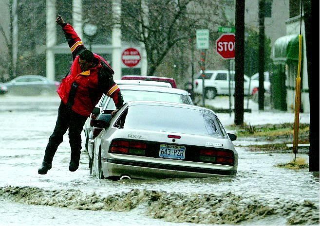 BRAD HORN/Nevada Appeal Ruben Correa, of Carson City, leaps over a car to get to his vehicle near Curry Street in Carson City on Saturday. A state of emergency was declared because of the flooding.