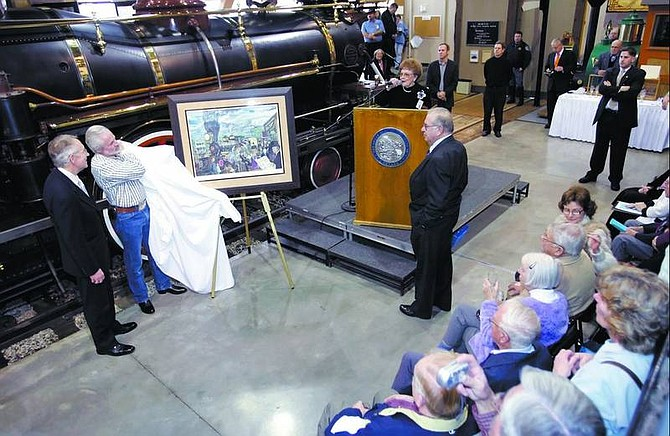 """Chad Lundquist/Nevada Appeal Carson City Mayor Marv Teixeira, in front of podium, and Janice Ayres, railway reconstruction commissioner, at podium, present Sen. Harry Reid, D-Nev., far left, with a commemorative painting during the """"silver spike"""" ceremony at the Nevada State Railroad Museum on Tuesday. Artist Steven Saylor unveils the watercolor. The ceremony commemorated completion of the first phase of the reconstruction of the V&T Railroad between Virginia City and Carson City."""
