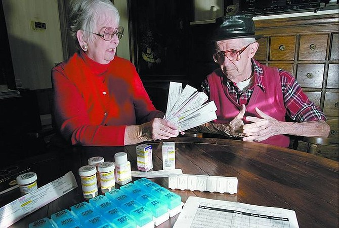 Chad Lundquist/Nevada Appeal Pauline and George Bauman, of Gardnerville, sit in their home on Sunday and look through prescription receipts from the past month. The Baumans are having to wait to fill prescriptions because of problems with the federal Medicare prescription plan.