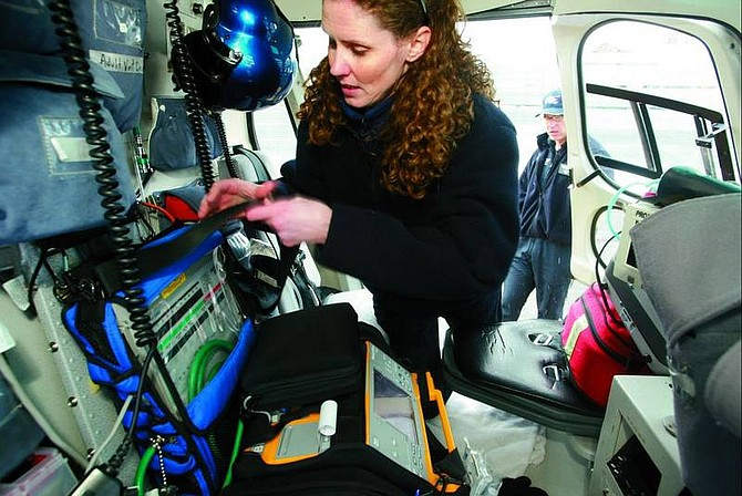 Photo by Ryan Salm Sierra Sun    ABOVE: Care Flight nurse Marti Robinson checks the medical equipment in the helicopter.  LEFT: Care Flight helicopter pilot Greg Poirier hovers over downtown Truckee as a snow storm makes its way into the region on Monday. Care Flight crews can respond to medical emergencies within a 150-mile radius of Truckee Tahoe Airport.  RIGHT: A Care Flight helicopter lifts off from its base at the fire station  in Martis Valley on Monday morning.