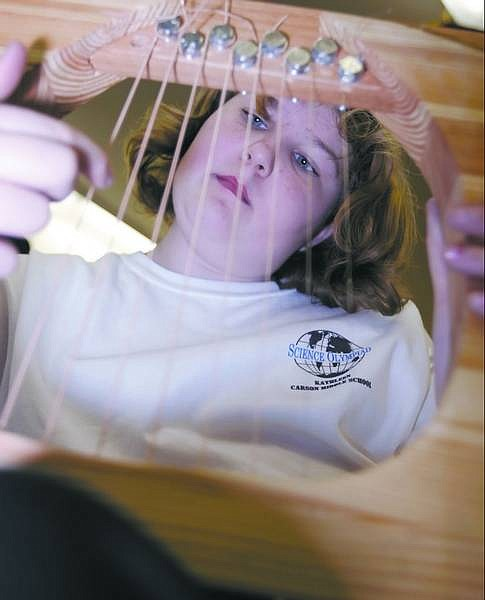"""Chad Lundquist/Nevada Appeal Thirteen-year-old Kathleen Bryant practices """"Aura Lee"""" on her handmade harp Wednesday afternoon at Carson Middle School. A team of 15 students from the middle school will compete in the state Science Olympiad on Saturday at Western Nevada Community College."""