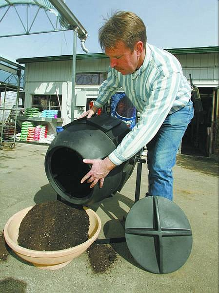 BRAD HORN/Nevada Appeal Dave Ruf, owner of the Greenhouse Garden Center, demonstrates the use of a compost barrel at his store.