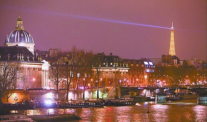 The Eiffel Tower shines over the Seine.