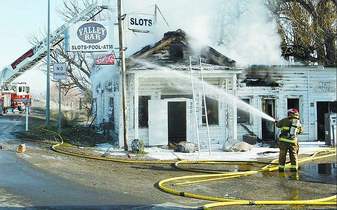 Jim Grant/Nevada Appeal News Service A firefighter douses a hot spot at the Valley Bar fire Sunday morning. The historic landmark, gathering place for locals and sometime polling place was destroyed.