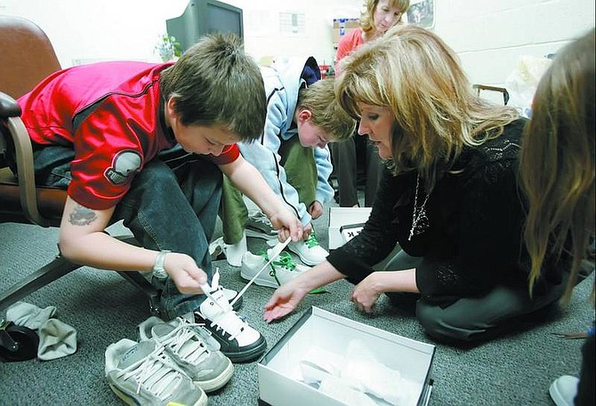 Kim Riggs, right, director of the Carson City School  District's Children-in-Transition program, helps  students at Fritsch  Elementary school try on new tennis shoes Monday. Fifty  students received a new pair of shoes through the district's Easter shoe drive, which still needs donations.   Chad Lundquist/ Nevada Appeal