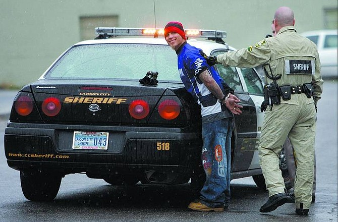 Chad Lundquist/Nevada Appeal Carson City Sheriff's deputies arrest Brett Court, 30, at the corner of East Park and Roop streets Tuesday. Court was arrested for allegedly robbing a man at knifepoint in a gas station parking lot.