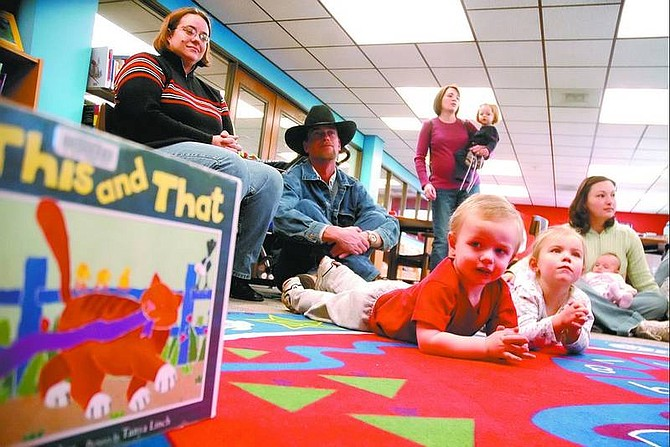 Kevin Clifford/Nevada Appeal William Koch, 2, from Dayton looks at a book while his sister Emily Koch, 3, and other parents and children listen to a children's story during family story time at the Carson City Library Friday morning.