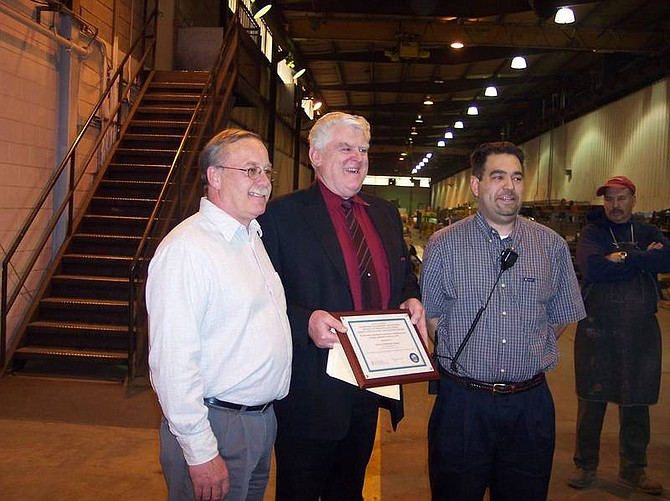 Submitted photo American Buildings Co. plant manager John Hinthorne, left, accepts the recognition certificate from Orville Reed, safety and health consultant for the state, center. Jose Rayo, right, is the company's human resources and safety manager.