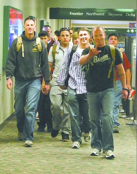BRAD HORN/Nevada Appeal Marines in the Fourth Force Recon Reserves, including Lance Cpl. Matthew Martin, gesturing, walk down the concourse toward their families at the Reno-Tahoe International Airport after returning from Iraq on Monday.