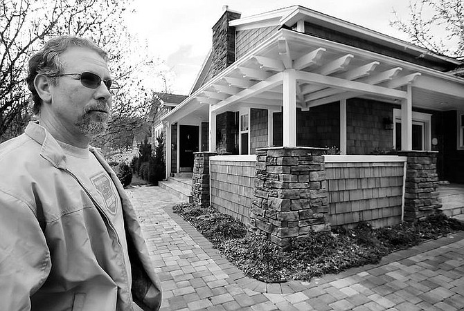 Chad Lundquist/Nevada Appeal Carson City's Historic Resources Commission Chairman Michael Drews stands at the Craftsman-style cottage owned by Karen Pecorilla. She won an award in 2004 for renovations of her historic 1004 W. King St. home.