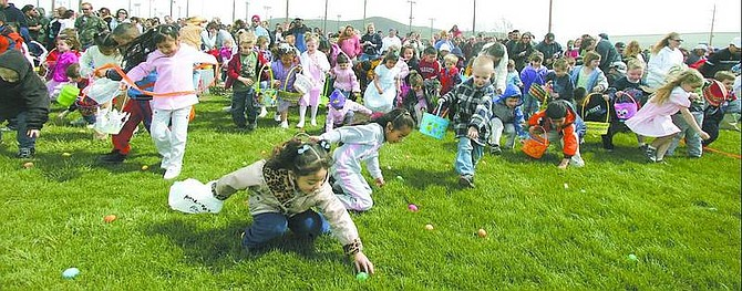BRAD HORN/Nevada Appeal File photo Children race to gather Easter eggs during the Jaycees' 29th annual Easter egg hunt at Governor's Field last year.
