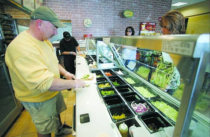 BRAD HORN/Nevada Appeal Tom Christian, owner of Subway off Topsy Lane in Indian Hills, slices avocado for a customer during lunch on Thursday.