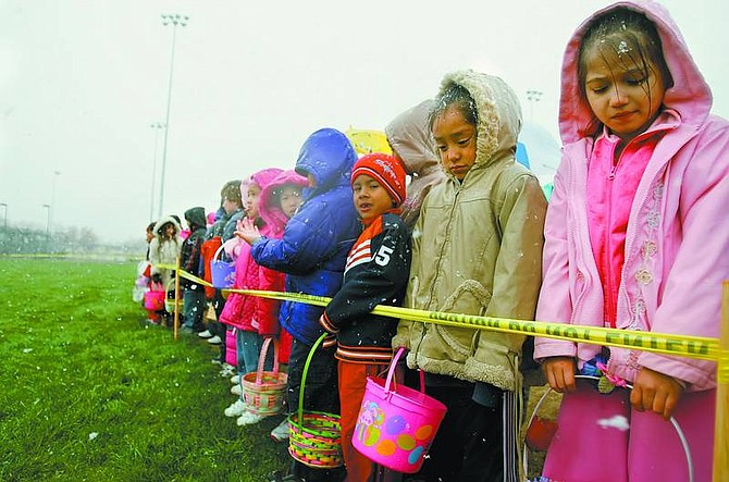 Chad Lundquist/Nevada Appeal Anxious children braving the cold, wet weather stand behind yellow caution tape awaiting the whistle blow to proceed onto Governors Field on Sunday in search for their share of the 30,000 dyed eggs.