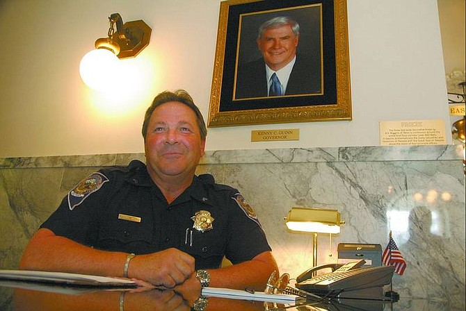 Kevin Clifford/Nevada Appeal Cpl. Randy Smith mans his post at the Capitol's front desk Friday afternoon. He has worked for the Capitol Police for 14 years, and has been a police officer for 37 years.
