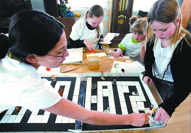 """Chad Lundquist/Nevada Appeal Briseida Hyatt, 12, Liz Howard, 12, Mariah Young, 11, Wendy Howard, 10, the four creators of the board game """"Ha Ha You Mythed Me,"""" work to finish parts of the game Tuesday. The girls hope their game will make a strong showing at the national TOYchallenge scheduled for April 29 in San Diego."""