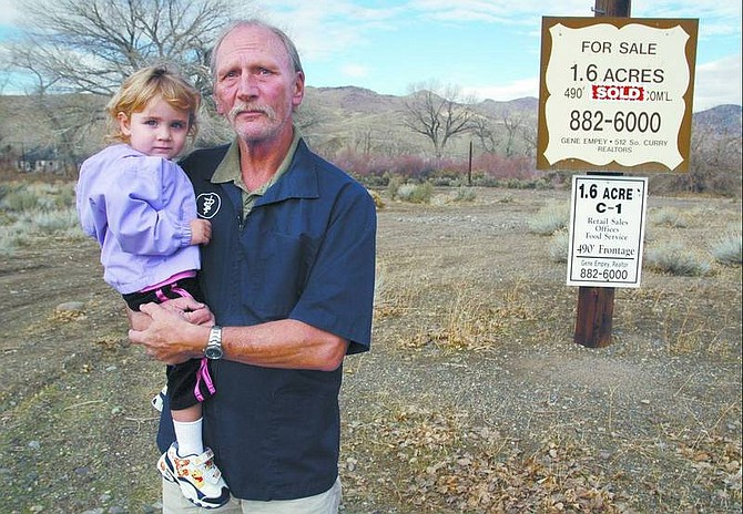 Kevin Clifford/Nevada Appeal Dr. Danny Larson and his daughter Kamalani, 2, stand on the future site of his veterinary hospital in this file photo. The building process has been delayed while water rights are being determined.