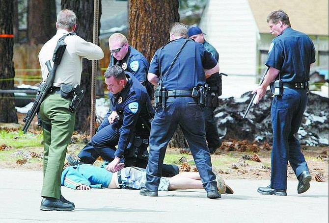 Jim Grant/Appeal News Service Police officers take Floyd Elmore into custody after he put down his weapon, ending a nearly three-hour standoff.
