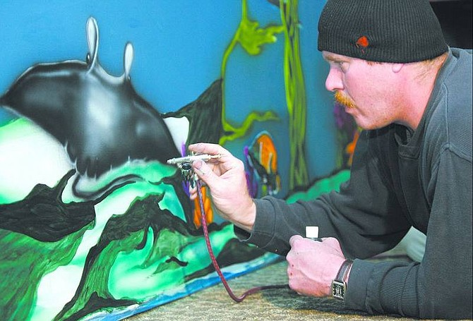 Cathleen Allison/Nevada Appeal Artist Robert Shipman airbrushes a mural at Fairl's on Friday afternoon. Owners Gene and Karen Fairl are revamping the bar as a tropical-themed teen club.