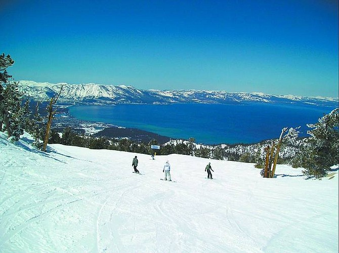 Lake Tahoe is an expanse of blue seen from the top of the usually  popular Ridge Trial, here with only four snowboarders enjoying the deep spring snow.         photos by Sam Bauman/Nevada Appeal
