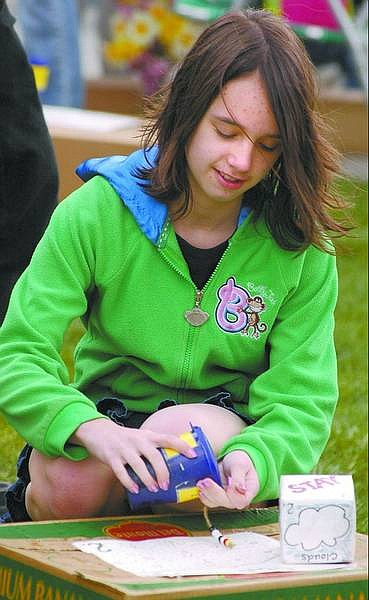 Kevin Clifford/Nevada Appeal Kelsey Machart, 12, of Carson City, collects beads Saturday afternoon while playing the Incredible Journey game at the Earth Day Fair, which was held at the Capitol Mall.