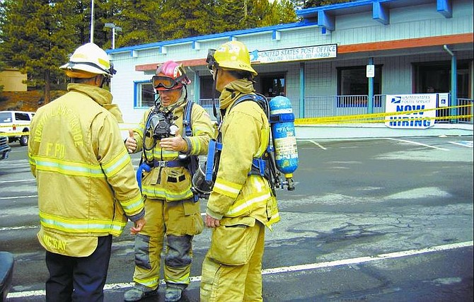 Erin Roth/Nevada Appeal News Service Fire district personnel wait outside the Incline Village Post Office for the health department to arrive to determine whether a suspicious substance found leaking from a manila envelope was hazardous. It proved to be cake frosting.