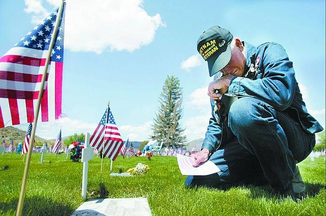 """Chad Lundquist/Nevada Appeal Overcome with tears, Vietnam veteran Steve Jazercak, 59, takes a moment to mourn at the grave of a friend's father. The man died in the Tet offensive in Vietnam, said Jazercak just after the Memorial Day Service at Lone Mountain Cemetery on Monday. """"I went to Vietnam with 10 of my friends and ended up burying eight of them"""" - one of whom was his high school friend."""