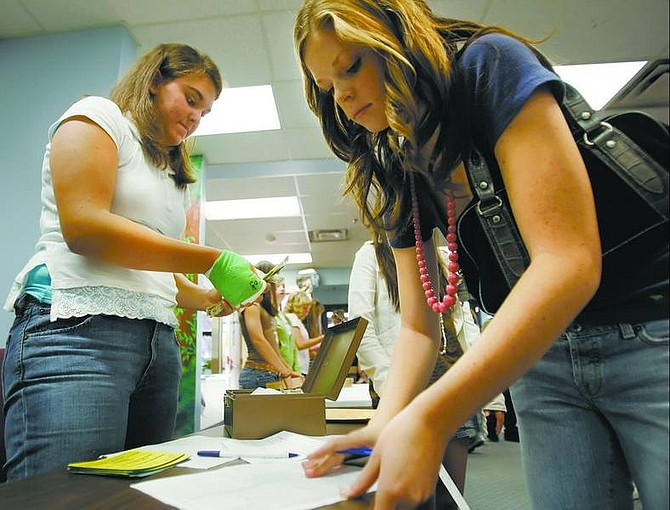 Chad Lundquist/Nevada Appeal Carson High School junior Heidi Flansberg counts money while senior Courtney Hutchins, both National Honor Society officers, signs out tickets Thursday for Friday's victory dance.