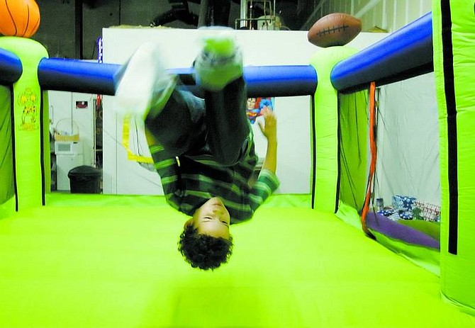 Brad Horn/Nevada Appeal Julius Estrada, 6, of Carson City, does a back flip in a bounce castle during a Christmas party at Bouncerz on Friday. Carson High School's National Honor Society raised money and bought gifts for six Carson City families and threw a Christmas party for them.