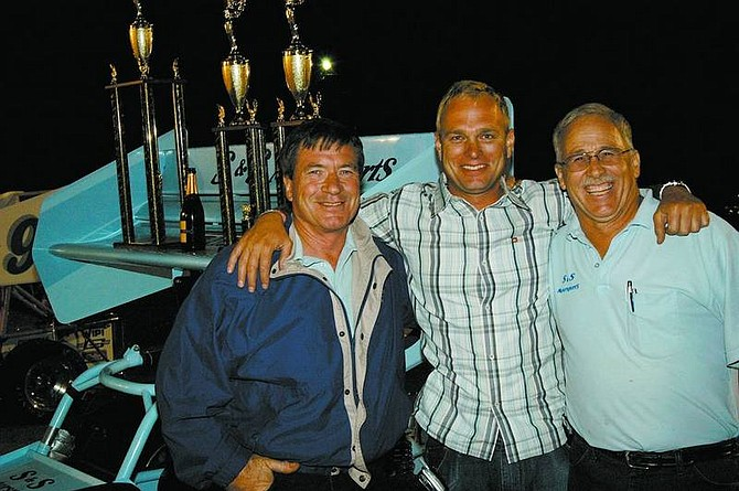 JACK RHYNE PHOTO S&S Motorsports owners Tom Silsby, left, and Steve Shaw, right, celebrate with driver Troy Regier after winning the 2005 Supermodified Racing League championship. The team also won the 2006 championship, winning seven out of nine feature races.