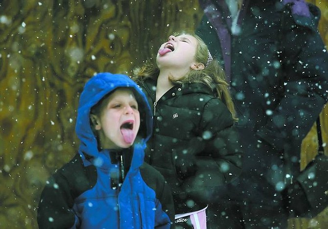 Brad Horn/Nevada Appeal Olivia Barnes, 9, tries to catch snow in her mouth with her brother Eddie Barnes, 6, in Virginia City on Thursday. The Barnes family, of Melbourne Beach, Fla., is visiting relatives in Dayton. This is the first time the children have seen snow, according to their mother.