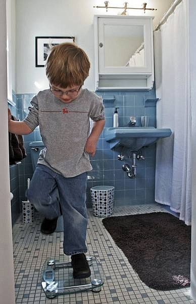 Tiles with vibrant colors _ such as lime green, lemon yellow and salmon pink, often paired with black _ can be traced to the art deco palettes of the 1930s and '40s, an expert says. The answer: Pull it out, cover it up or make it work. Isaac Orrell, 5, of McLean, Va., in his family's circa-1968 blue bathroom. Illustrates DESIGN-TILE (category l), by Terri Sapienza (c) 2007, The Washington Post. Moved Thursday, Jan. 25, 2007. (MUST CREDIT: Washington Post photo by Bill O'Leary.)