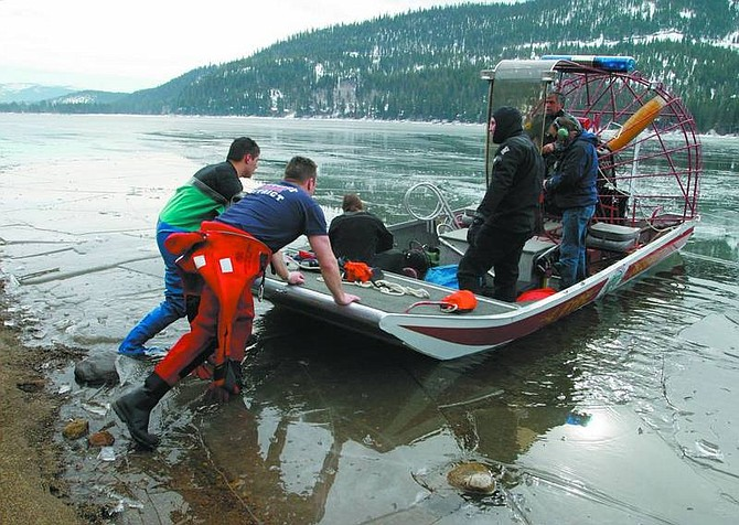 Emma Garrard/Appeal News Service Truckee Fire Protection District firefighters Ryan Ochoa and Eric Jitloff push a Fire Rescue boat out onto Donner Lake in an attempt to rescue a man who fell through the ice Friday morning. The body has yet to be recovered from the Lake.