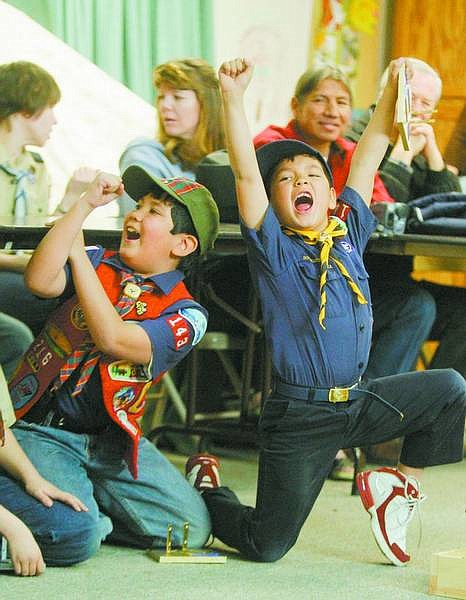 BRAD HORN/Nevada Appeal Zachary Frewert, 8, right, celebrates after winning a heat at Pack 143's pinewood derby at St. Paul's Church on Saturday. On the left is Frewert's brother Ricky, 9. Zachary placed first overall while Ricky took second.