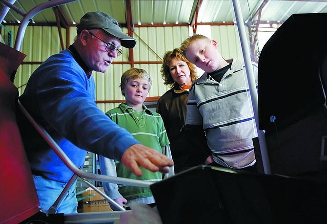 Chad Lundquist/Nevada Appeal  Mike Reynolds, left, and Merry Romine, center, show Caulin Schadeck, 9, and his brother Caleb, 11, the construction progress on Reynolds H-Air light sport airplane as part of the young eagles program.