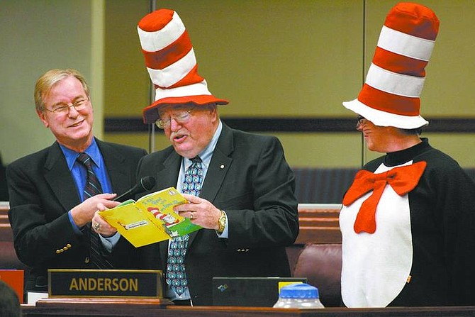 """Nevada Assemblyman David Parks, D-Las Vegas, holds the microphone as Assemblyman Bernie Anderson, D-Sparks, reads a Dr. Seuss book Friday morning at the Legislature. Anderson and Lynn Warne, right, with the Washoe Education Association, were recognizing """"Read Across America"""" day during the Assembly floor session.  Cathleen Allison/Nevada Appeal"""