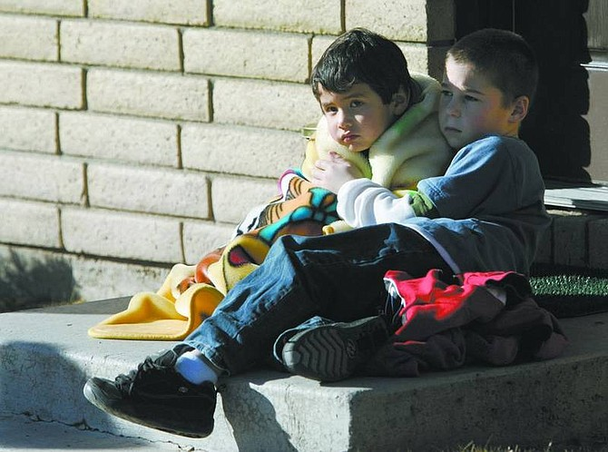 One of five children evacuated from a Woodside Drive apartment is comforted by a friend Friday afternoon following a fire that destroyed one room of the family's apartment.