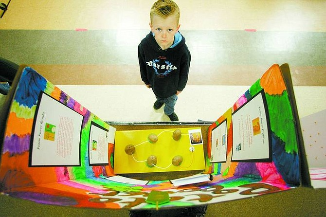 Taylor Saarem,     8, a second-grade     student at Fritsch   Elementary School, stands in front of a science fair project in the gym.  BRAD HORN/ Nevada Appeal