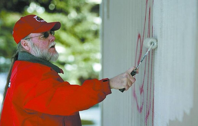 Cathleen Allison/Nevada Appeal Volunteer Marvin Inman paints over graffiti on Allouette Way on Wednesday afternoon.