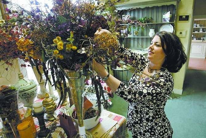 Cathleen Allison/Nevada Appeal Heather Blueberg, co-owner of Chateau Bliss, works on a flower arrangement Friday at the Carson City shop. After three years, the boutique has closed its doors.