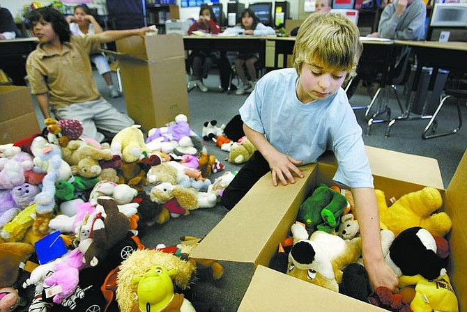 Cathleen Allison/Nevada Appeal Bordewich-Bray Elementary School leadership members Gehrig Tucker, 11, right, and Anthony Burchett, 10, sort stuffed animals Thursday at the school. Students collected the toys to be donated to children in Baghdad.