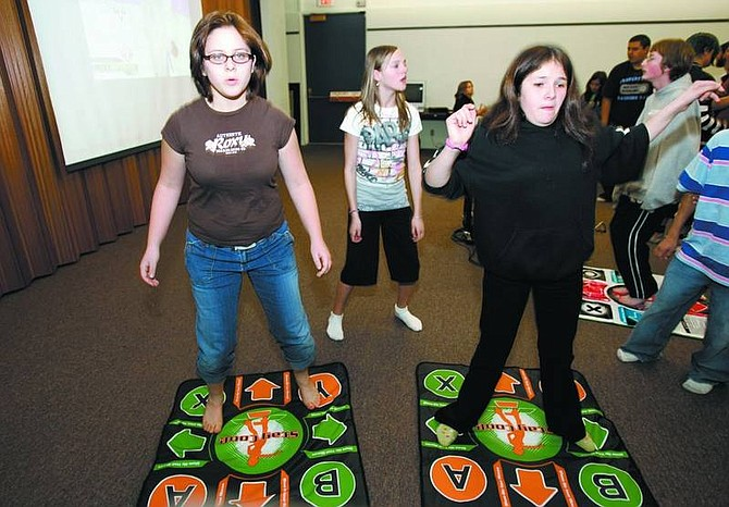 """Chad Lundquist/Nevada Appeal Megan Nelson, 12, Leah Wegner, 12, and Destiny Martinez, 15, move their feet to the signals on a screen during the """"Dance Dance Revolution"""" tournament on Tuesday at the Carson City Library."""