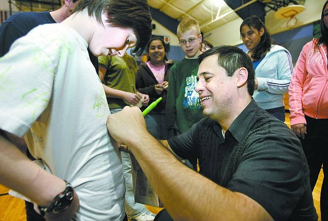 """Cathleen Allison/Nevada Appeal Olympian Ruben Gonzalez autographs Ryan Sawyer's shirt at Dayton Intermediate School on Thursday. Sawyer, 11, thought it was """"pretty sick"""" to meet Gonzalez, a former Olympic luger who now works as an inspirational speaker traveling the country encouraging people to read and to follow their dreams."""