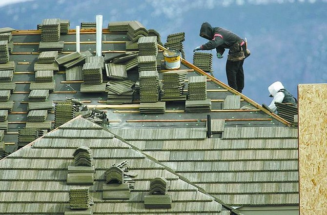 Cathleen Allison/Nevada Appeal Workers install a roof on a new home in the Santa Maria Ranch area Wednesday.