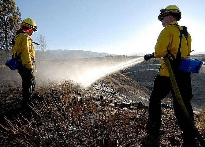 Sparks firefighters Matt Joseph, right, and Mike Foster water down hot spots after a fire behind Heights Drive in Reno, Nev., Saturday, March 17, 2007. (AP Photo/Nevada Appeal, Kevin Clifford)