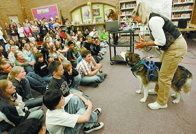 Chad Lundquist/Nevada Appeal Lorraine Temple of Homer, Alaska, and her husky, Buckeye, demonstrate how a sled dog harness works during a presentation at Eagle Valley Middle School on Tuesday.