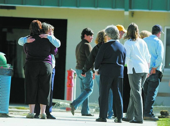 BRAD HORN/Nevada Appeal Sutro Elementary School employees gather near the scene after Judy Perez's Jeep Grand Cherokee Ladero tore through a fence  when her brakes failed in the school's parking lot on Thursday morning in Dayton.